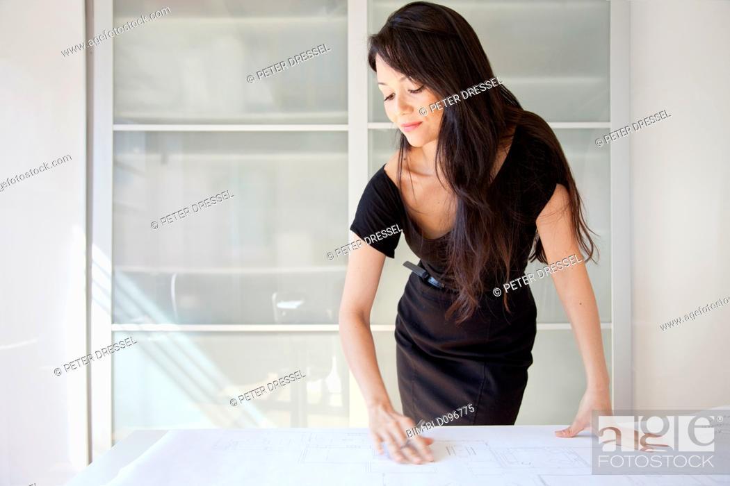 Stock Photo: Mixed race businesswoman looking at blueprints in office.