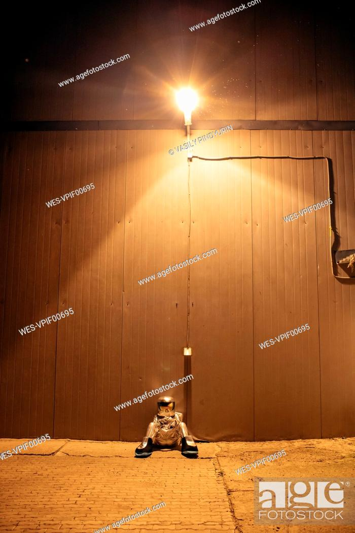Imagen: Spaceman sitting under lamp at a wall at night.