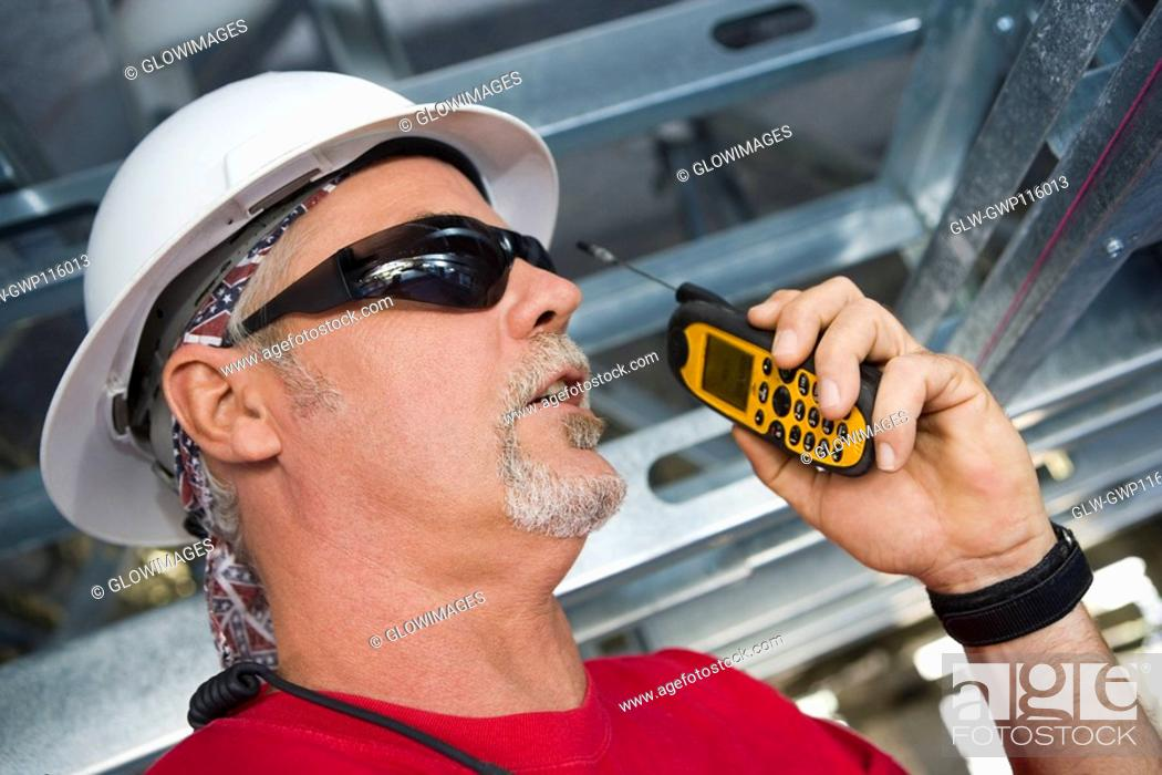 Stock Photo: Close-up of a male construction worker talking on a walkie-talkie.