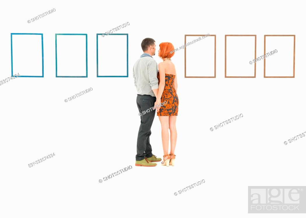 Imagen: man and woman holding hands in front of empty frames displayed on white walls.