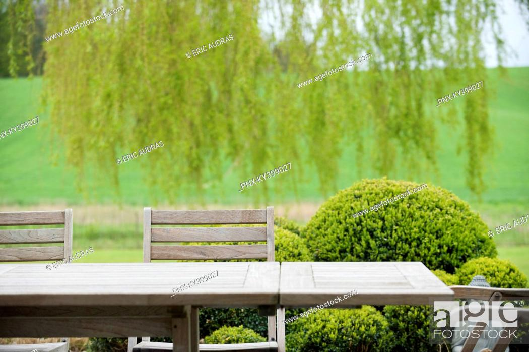 Stock Photo: Table with chairs in a garden.