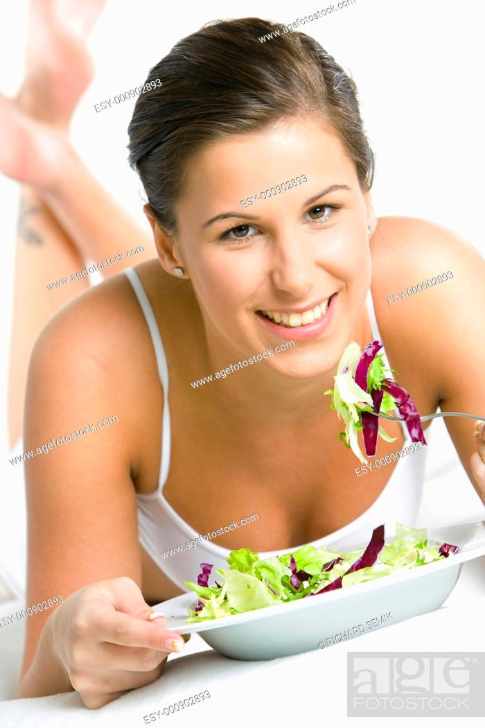 Stock Photo: portrait of lying down woman eating salad.