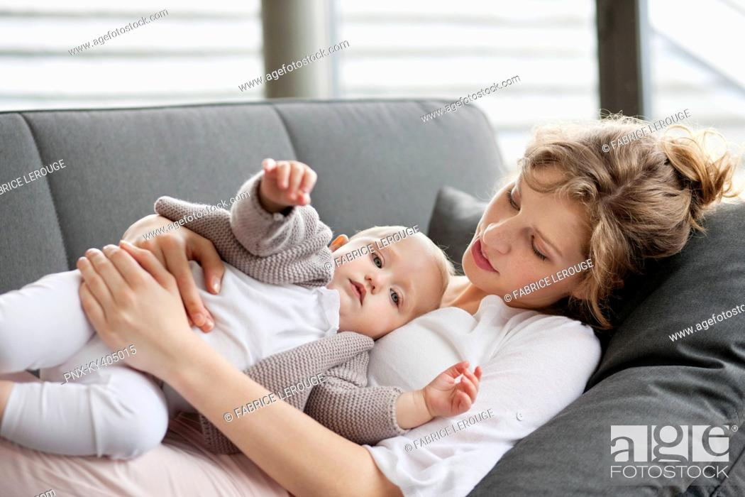 Stock Photo: Woman resting on a couch with her daughter.