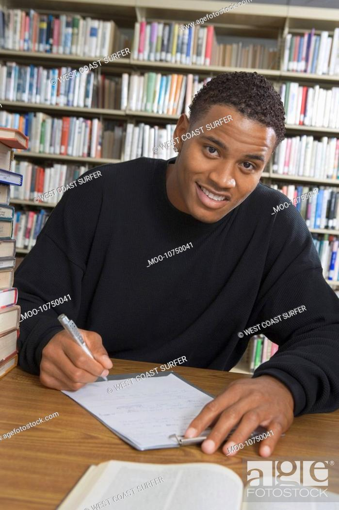 Stock Photo: Male student making notes in college library.