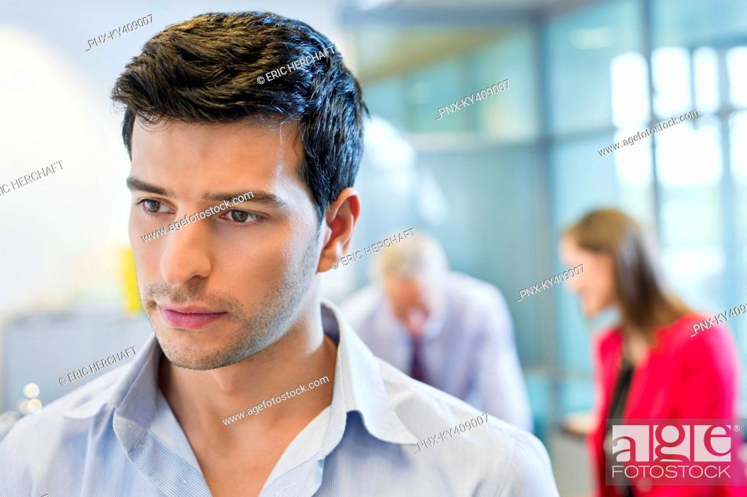 Stock Photo: Male executive thinking in an office with his colleagues discussing in the background.