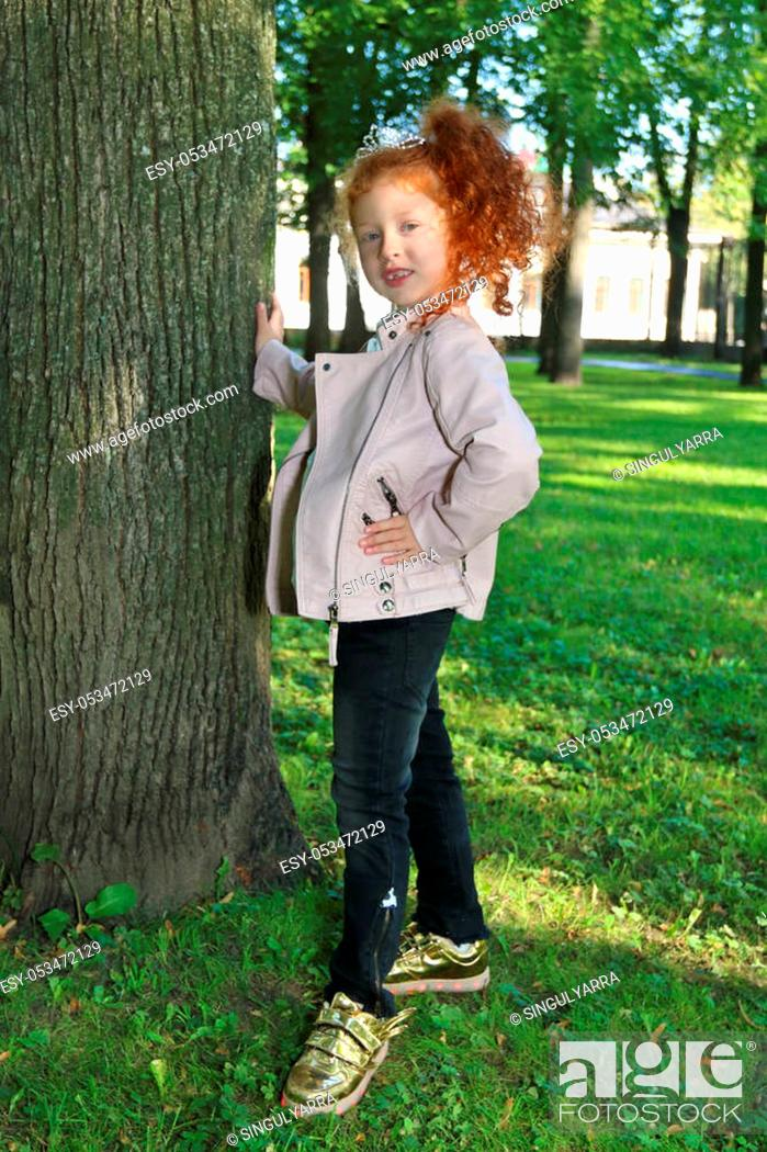 Stock Photo: Little girl with red hair in leather jacket poses near tree in summer green park.