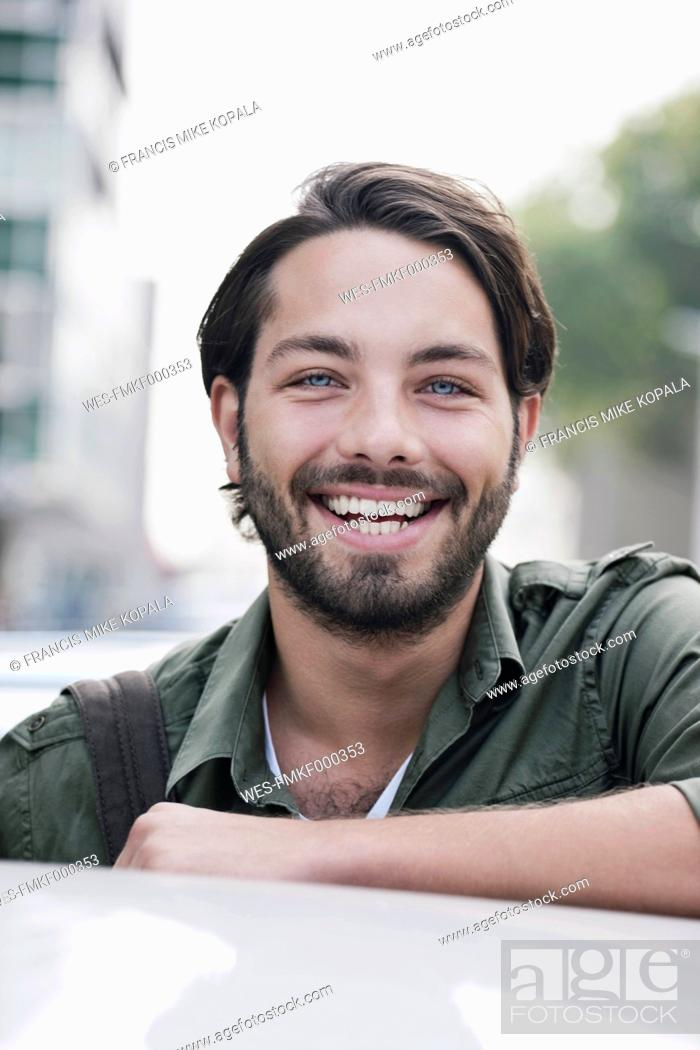 Stock Photo: Germany, Cologne, Young man near car, smiling, portrait.