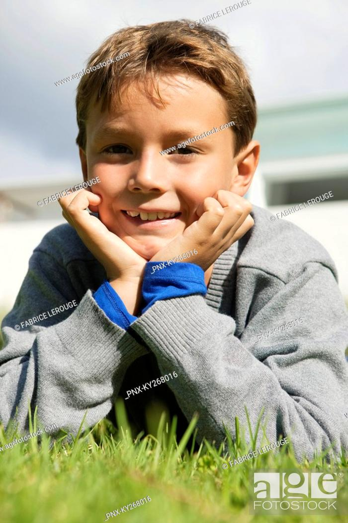 Stock Photo: Boy lying on grass and smiling.