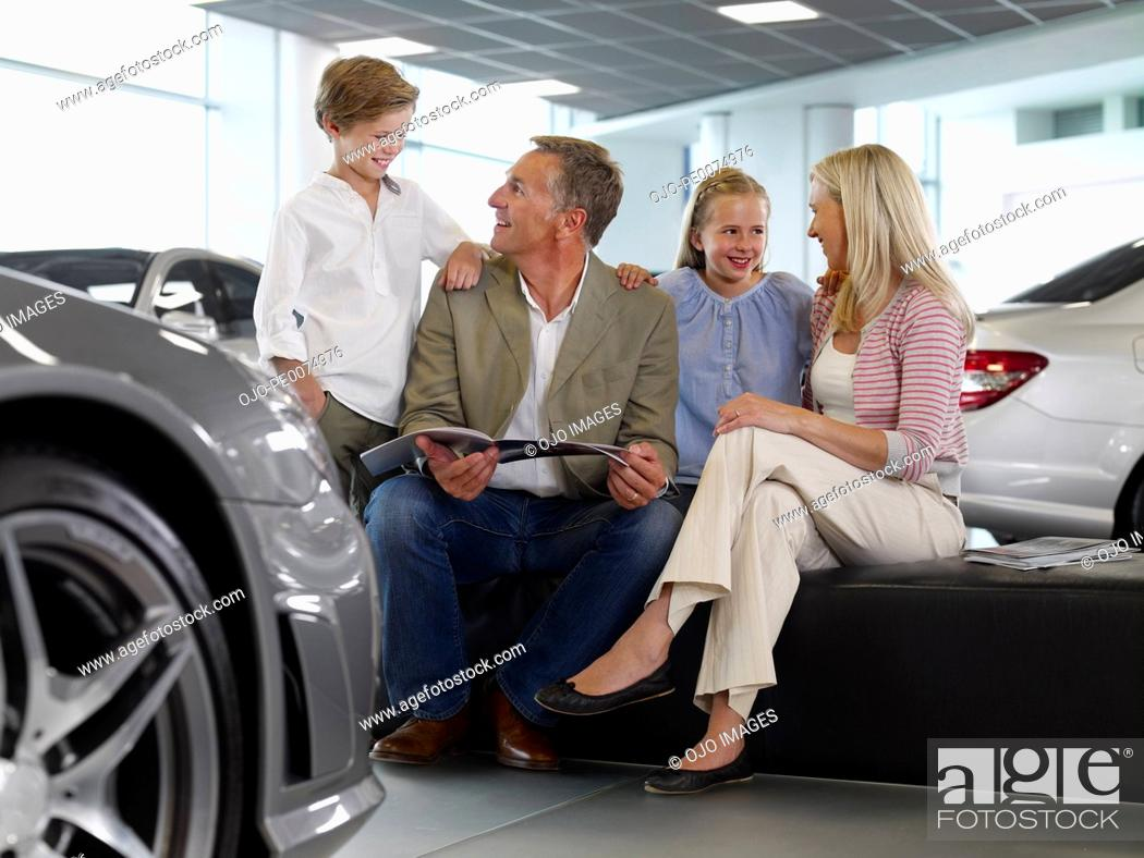 Stock Photo: Family looking at brochure in automobile showroom.