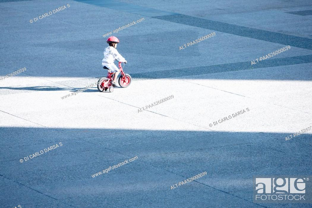 Stock Photo: Child riding bicycle alone in public square.