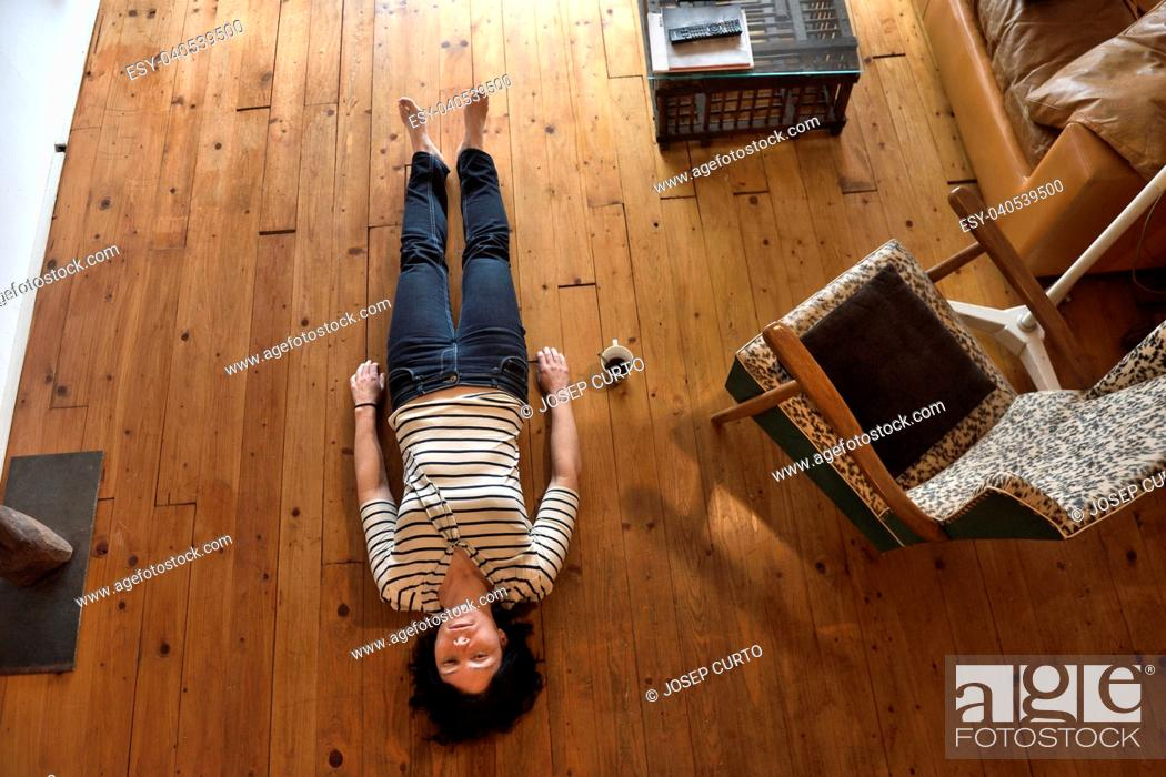 Stock Photo: a woman lying on the floor of her house.