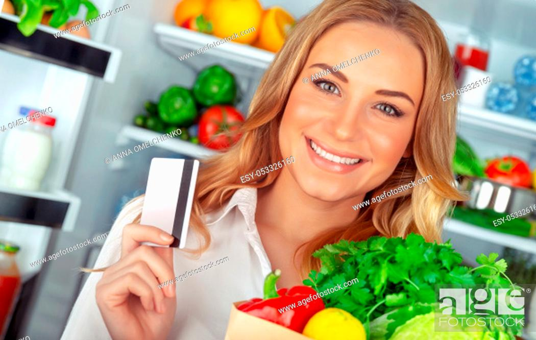 Stock Photo: Healthy nutrition concept, portrait of a beautiful young woman standing near open refrigerator with a full paper bag of a fresh vegetables, holding credit card.