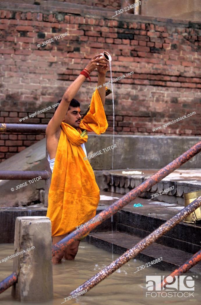 Stock Photo: Man taking ritual bath in the river Ganga. Ganges. The holy city of Varanasi, India.