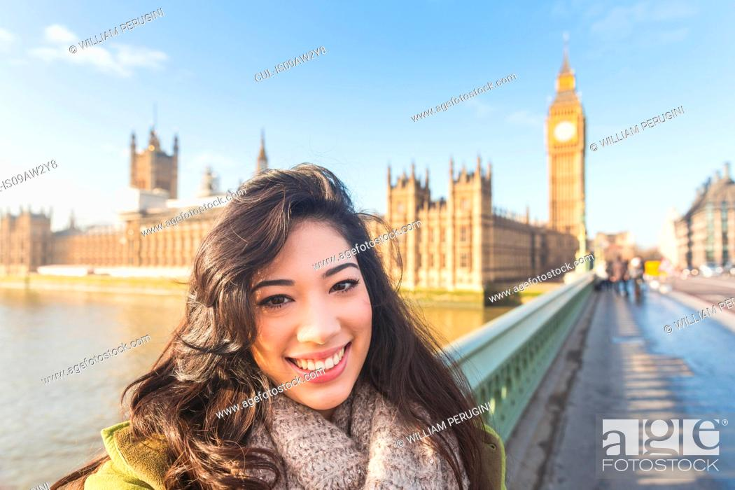 Stock Photo: Portrait of young woman on Westminster bridge looking at camera smiling, Thames river, London, UK.