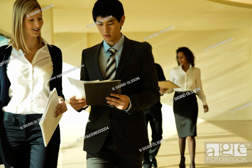 Stock Photo: Business associates walking and discussing documents.