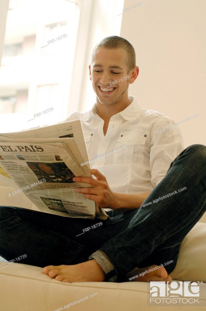 Imagen: Man reading newspaper on couch.