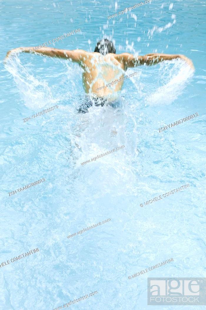 Stock Photo: Man swimming and splashing in pool, rear view.