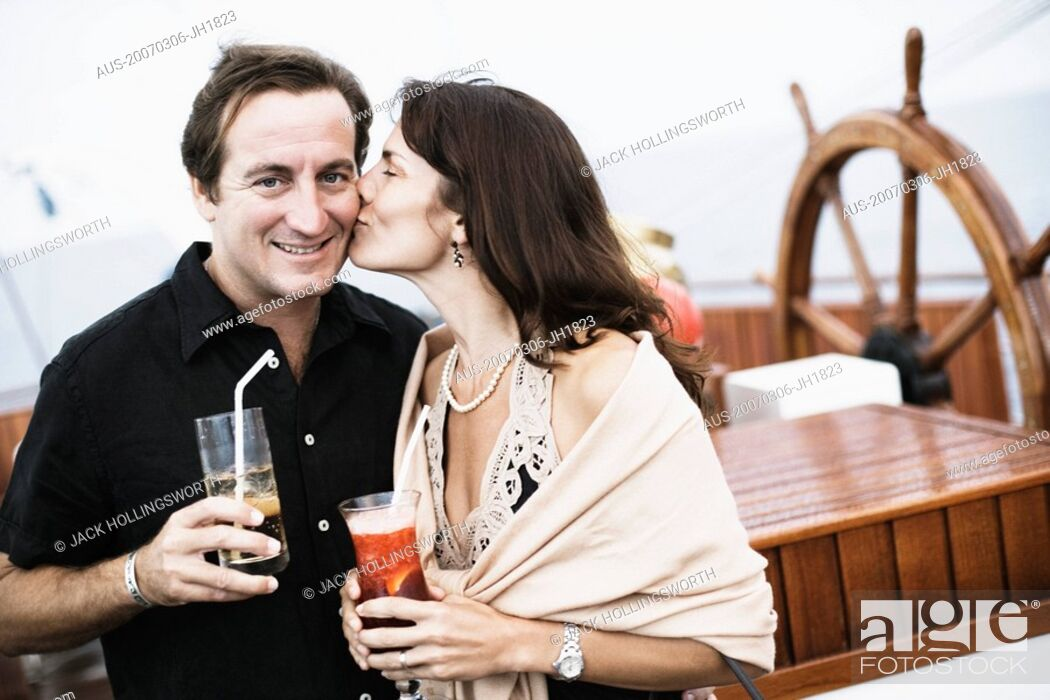 Stock Photo: Mid adult woman kissing a mid adult man on a sailing ship.