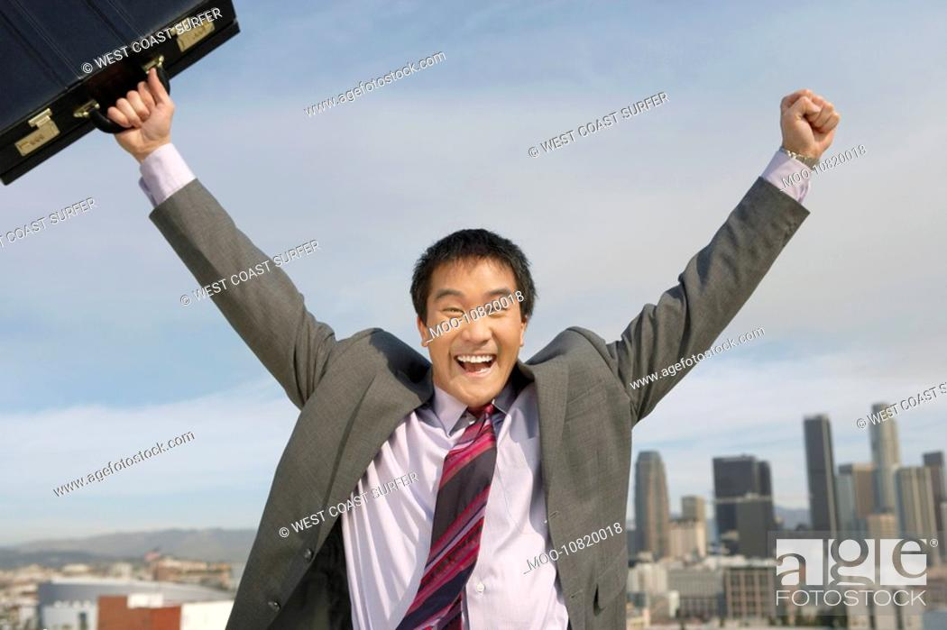 Stock Photo: Business man cheering in city.