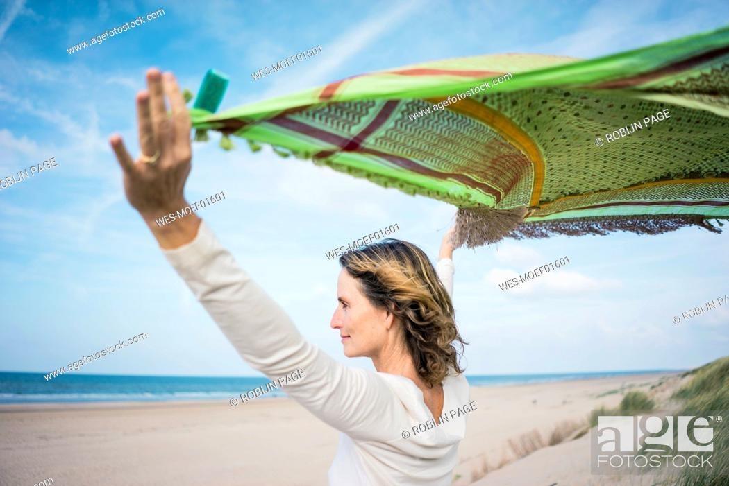 Stock Photo: Mature woman holding flapping scarf in the wind, relxiang in the dunes.