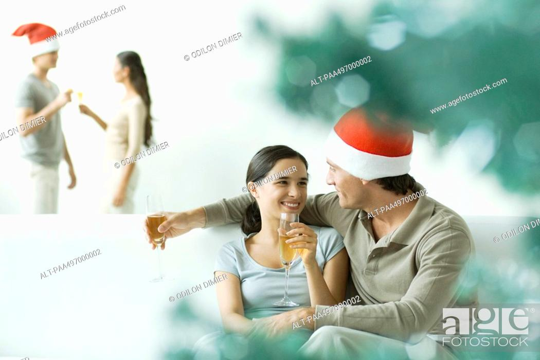 Stock Photo: Couple sitting on sofa, drinking champagne, man wearing Santa hat.