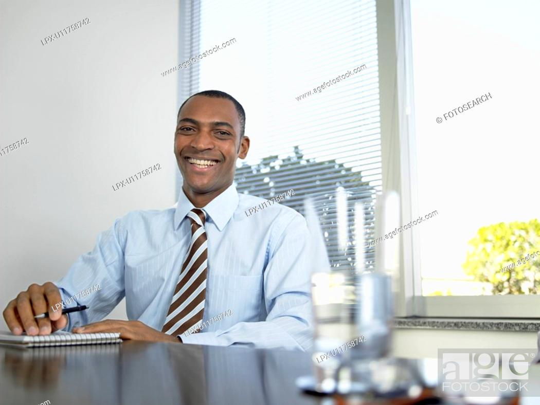 Stock Photo: Businessman laughing by table portrait.