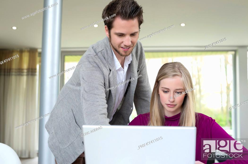 Stock Photo: Woman working on a laptop with a man standing beside her.