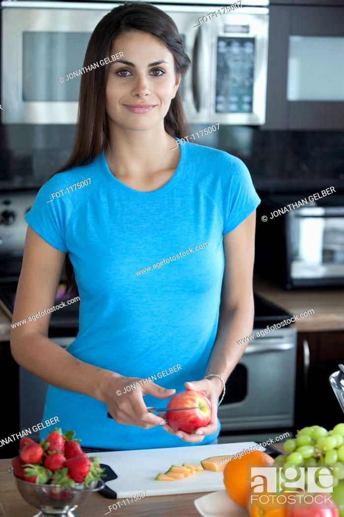 Stock Photo: Woman preparing fruit in kitchen.