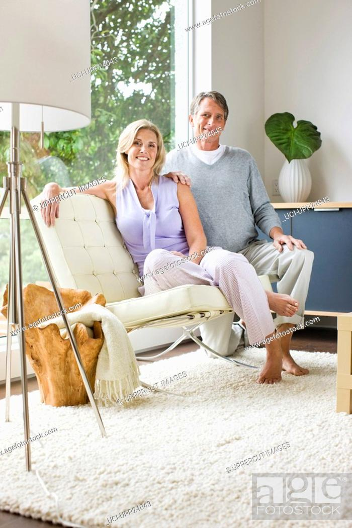 Stock Photo: Portrait of couple sitting in living room.