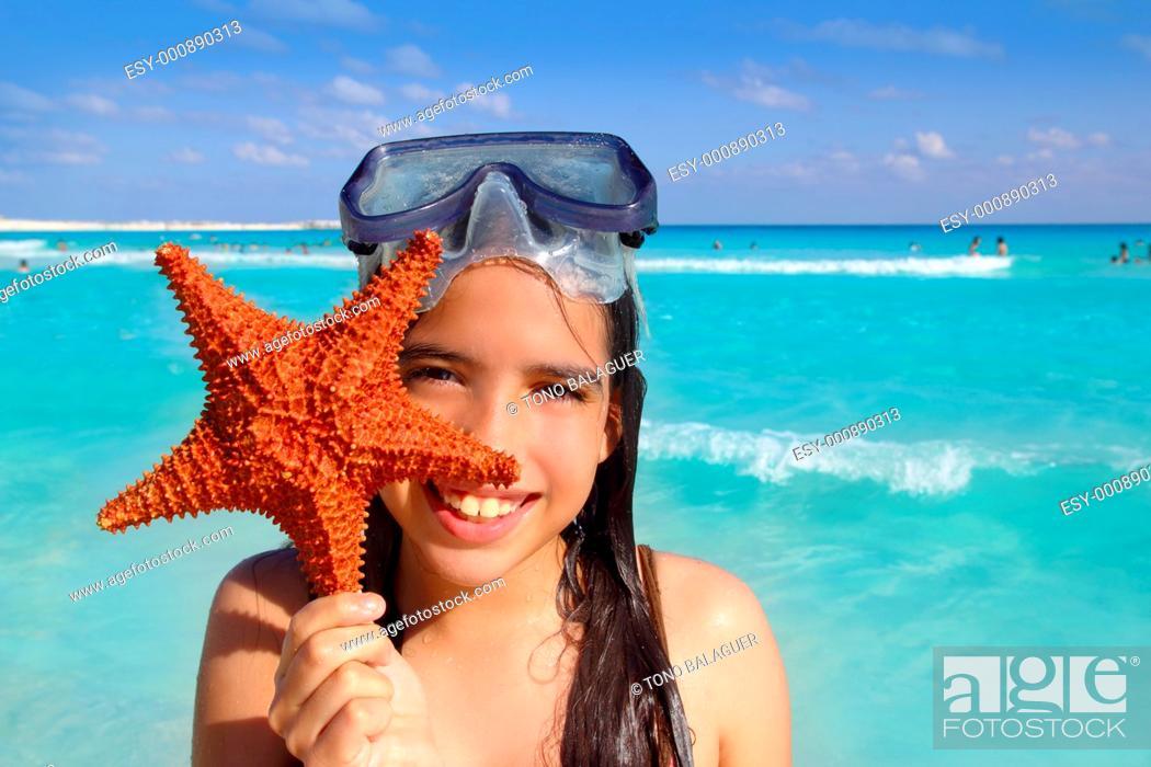 Stock Photo: latin tourist girl holding starfish in tropical beach.