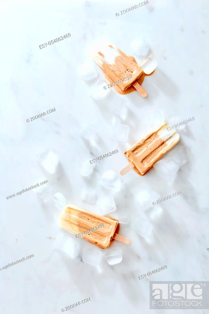 Stock Photo: Sweet creamy coffee ice cream on a stick with ice cubes in a gray marble table with space for text. Homemade refreshing dessert. Flat lay.