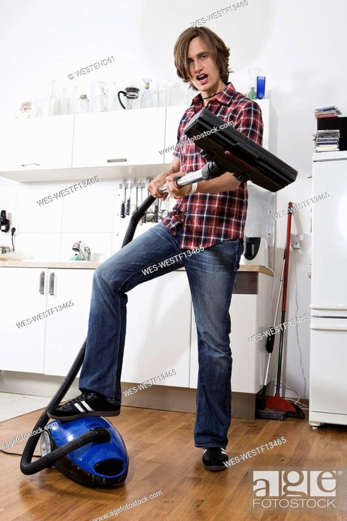 Stock Photo: Germany, Berlin, Young man with vacuum cleaner, portrait.