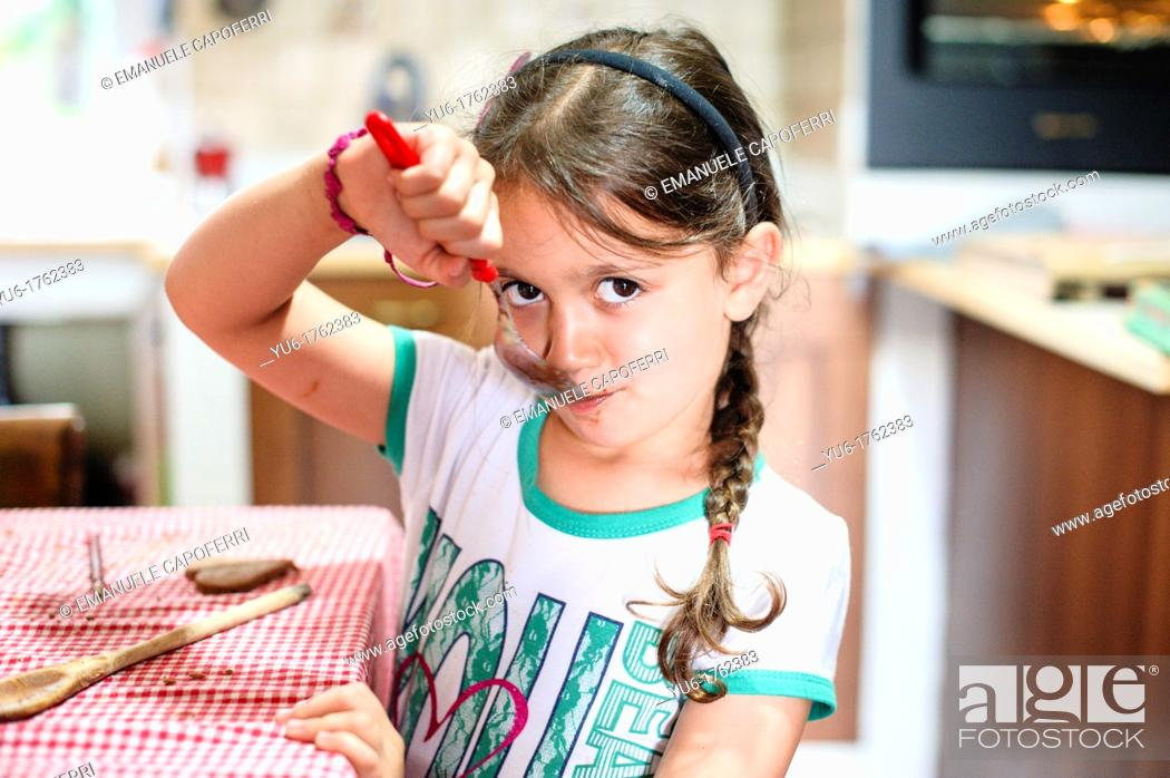 Stock Photo: Children lick spoon with chocolate.