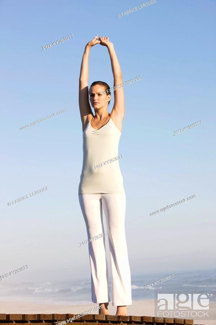 Stock Photo: Woman stretching her arms on a boardwalk.