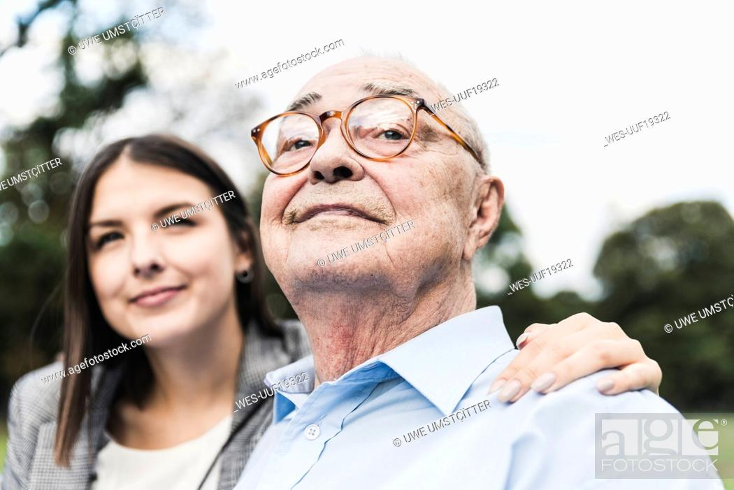 Stock Photo: Portrait of self-confident senior man with granddaughter in the background.