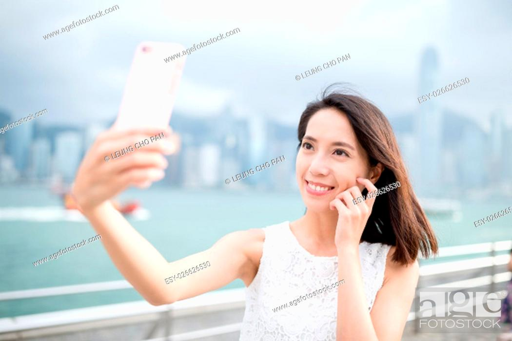 Stock Photo: Woman taking self image by mobile phone.