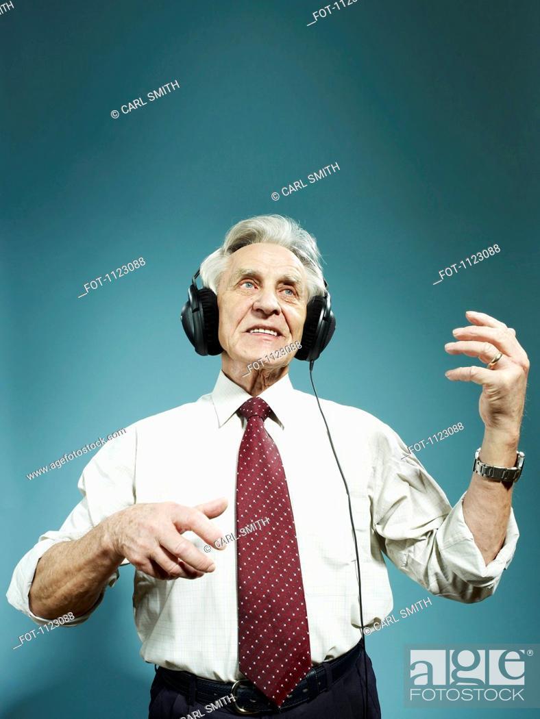 Stock Photo: A senior man wearing headphones and playing air guitar.