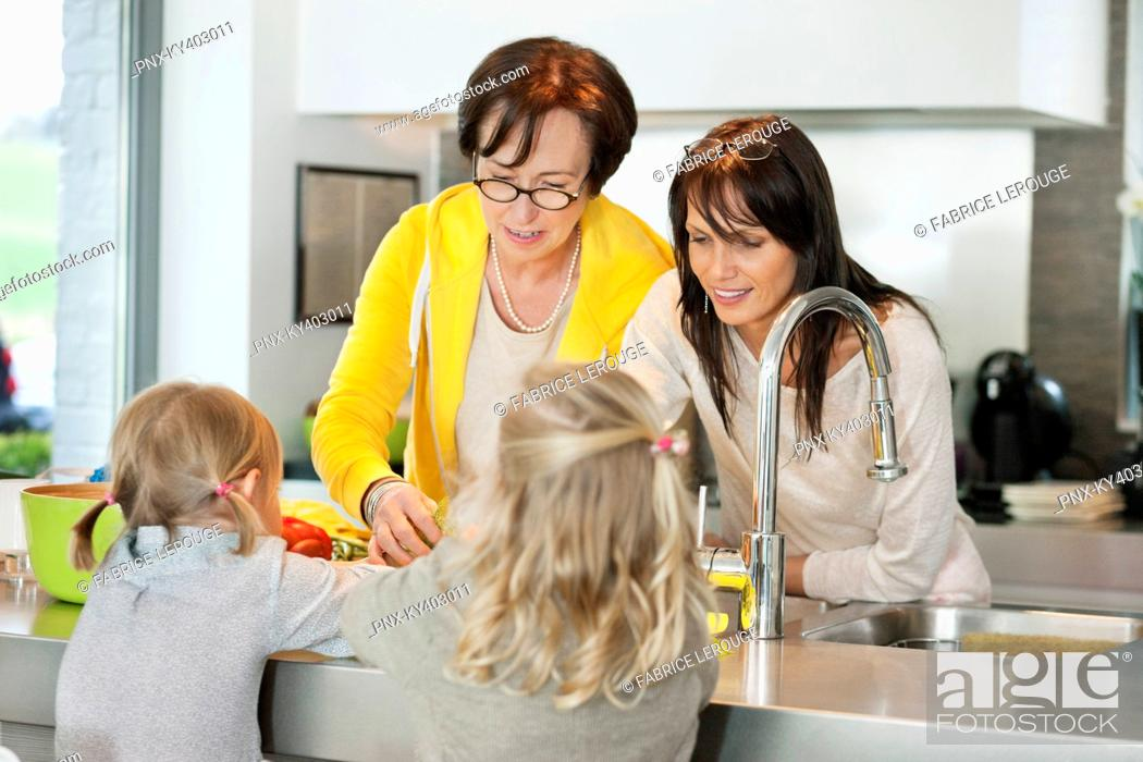 Stock Photo: Two girls with her mother and grandmother working in a kitchen.