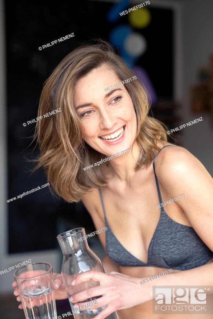 Stock Photo: Portrait of laughing woman with water bottle and glass of water.