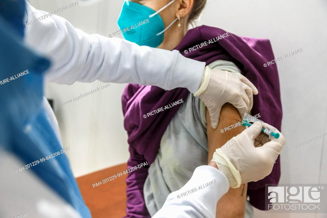 Stock Photo: 29 December 2020, Hamburg: A young woman receives a fictitious vaccination as a test vaccinee during a trial run of the Hamburg Corona Vaccination Centre.