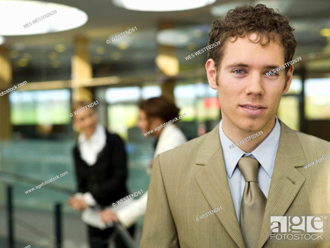Stock Photo: Young businessman, portrait, women in background.