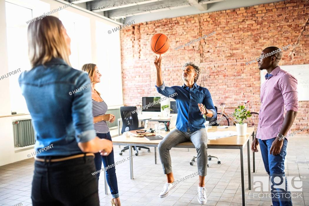 Stock Photo: Colleagues playing basketball in office.