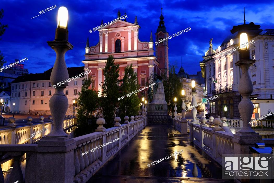 Stock Photo: Reflections on wet Triple Bridge after rain at dawn with lights on Franciscan Church of the Annunciation and Central Pharmacy Ljubljana Slovenia.