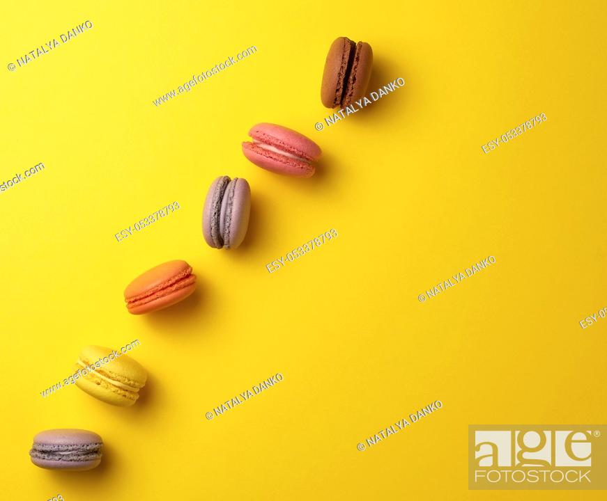 Stock Photo: assortment of multi-colored baked round macarons on a yellow background, flat lay, copy space.