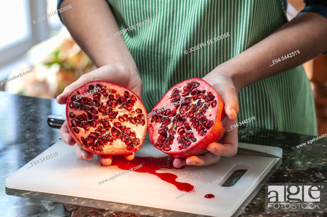 Stock Photo: A cross secetion of a half Pomegranate, expsosing rind and seeds.