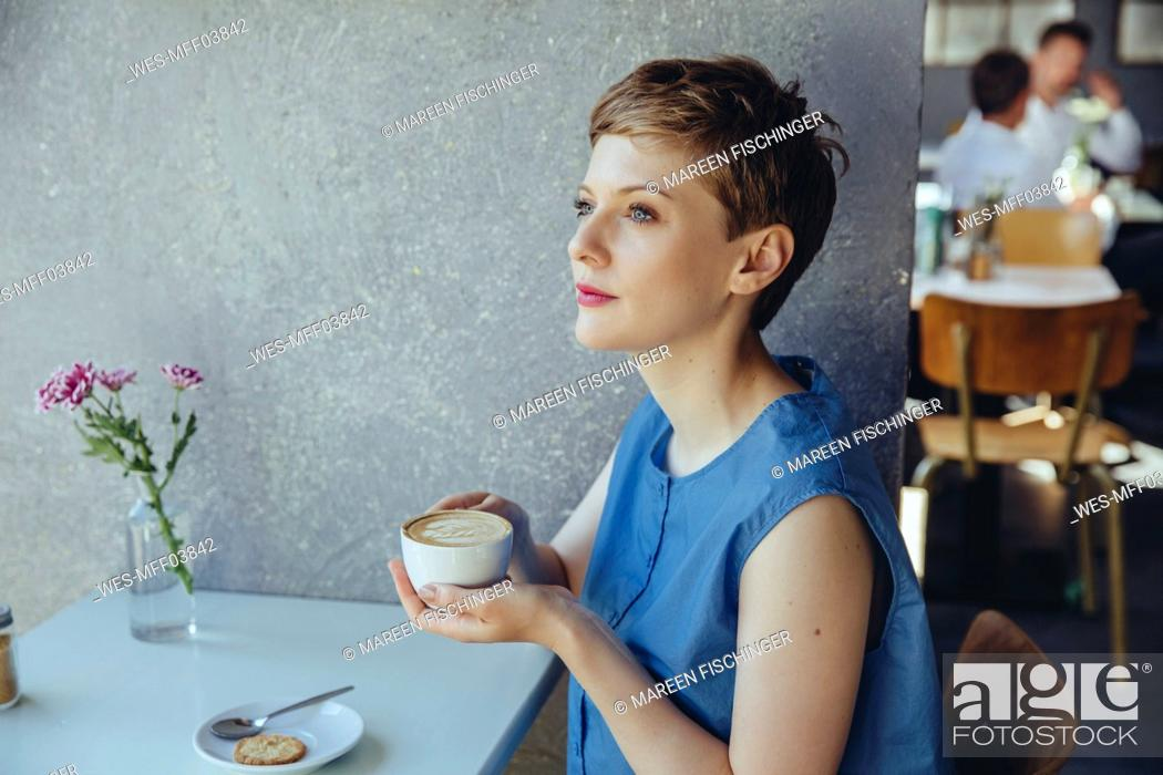 Stock Photo: Serious woman with a cup of coffee in a cafe.