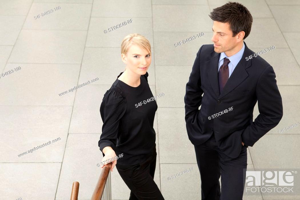 Stock Photo: Two businesspeople in lobby, Munich, Bavaria, Germany.