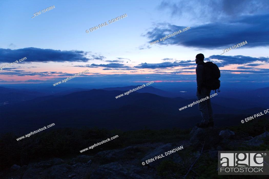 Stock Photo: A hiker ascending the Jewell Trail enjoys the views at sunset  Located in the White Mountains, New Hampshire USA.