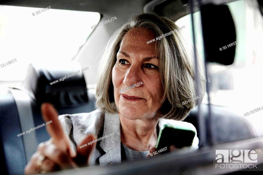 Photo de stock: Senior businesswoman sitting in back of taxi, holding smartphone, giving directions to driver.