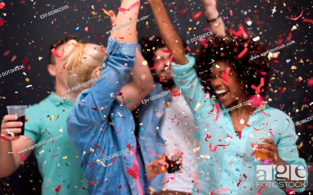 Photo de stock: confetti party Multiethnics group of happy young people celebrating new year eve while dancing and have fun at home.